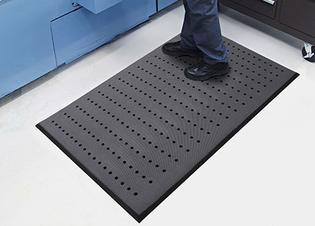 A healthcare professional standing on an anti-fatigue mat