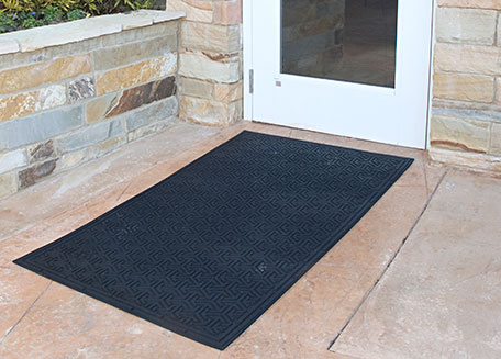 A specialty floor mat placed outside of an entryway