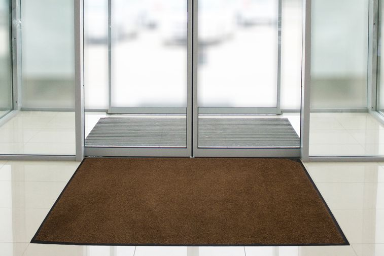 A Traditional walk off floor mat placed in an entryway